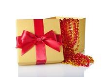 Χρυσό κλασικό λαμπρό ανοικτό κιβώτιο δώρων με το κόκκινο τόξο σατέν και τη διακοσμημένη με χάντρες γιρλάντα Στοκ φωτογραφία με δικαίωμα ελεύθερης χρήσης
