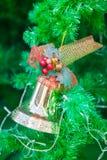 Χρυσό κουδούνι με την κόκκινη διακόσμηση κορδελλών στο χριστουγεννιάτικο δέντρο Στοκ Φωτογραφία