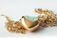 Χρυσό κρεμαστό κόσμημα σε μια χρυσή αλυσίδα χρυσή καρδιά Στοκ Φωτογραφία