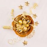 Χρυσό κύπελλο με τα αστέρια Χριστουγέννων, σφαίρες, κορδέλλες στο λευκό ξύλινο πίνακα, τοπ άποψη Στοκ φωτογραφία με δικαίωμα ελεύθερης χρήσης