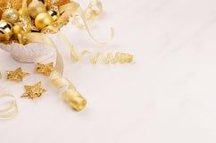 Χρυσό κύπελλο με τα αστέρια Χριστουγέννων, σφαίρες, κορδέλλες στο λευκό ξύλινο πίνακα, θαμπάδα Στοκ Εικόνες