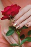 Χρυσό μανικιούρ Το θηλυκό χέρι που κρατά κόκκινο αυξήθηκε Στοκ εικόνα με δικαίωμα ελεύθερης χρήσης