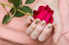 Χρυσό μανικιούρ Το θηλυκό χέρι που κρατά κόκκινο αυξήθηκε Στοκ Φωτογραφία