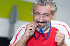 Χρυσό μετάλλιο δαγκώματος ατόμων Στοκ φωτογραφία με δικαίωμα ελεύθερης χρήσης