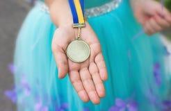 Χρυσό μετάλλιο στο χέρι κοριτσιών Βαθμολογημένος από τον παιδικό σταθμό στοκ εικόνες με δικαίωμα ελεύθερης χρήσης
