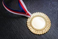 Χρυσό μετάλλιο - βραβείο για έναν νικητή στο μαύρο υπόβαθρο Στοκ Φωτογραφίες
