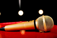 Χρυσό μικρόφωνο στο σκοτεινό υπόβαθρο με πολλά φω'τα Στοκ φωτογραφία με δικαίωμα ελεύθερης χρήσης