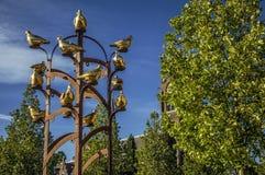 Χρυσό μνημείο πουλιών μετάλλων με το φυλλώδες δέντρο και καμπαναριό στην ηλιόλουστη ημέρα σε Weesp Στοκ φωτογραφίες με δικαίωμα ελεύθερης χρήσης