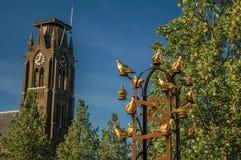 Χρυσό μνημείο πουλιών μετάλλων με το φυλλώδες δέντρο και καμπαναριό στην ηλιόλουστη ημέρα σε Weesp Στοκ Εικόνες