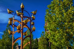 Χρυσό μνημείο πουλιών μετάλλων με το φυλλώδες δέντρο και καμπαναριό στην ηλιόλουστη ημέρα σε Weesp Στοκ φωτογραφία με δικαίωμα ελεύθερης χρήσης