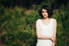χρυσό μοντέλο μόδας φορεμ Κορίτσι με το χαριτωμένο hairstyle στη φύση Στοκ Εικόνα