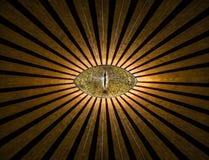 Χρυσό να όλος-δει ανώνυμο μάτι με το αφηρημένο υπόβαθρο θρησκείας γραμμών και φω'των Στοκ φωτογραφία με δικαίωμα ελεύθερης χρήσης