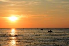 Χρυσό τροπικό ηλιοβασίλεμα, σκιαγραφία των ψαράδων στον ορίζοντα Στοκ Εικόνες