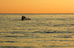 Χρυσό τροπικό ηλιοβασίλεμα, σκιαγραφία των ψαράδων στον ορίζοντα Στοκ Φωτογραφίες