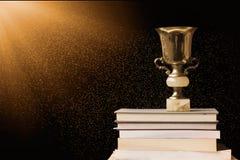 Χρυσό τρόπαιο στο σωρό των βιβλίων, ενάντια στον πίνακα, με την ακτίνα ήλιων Στοκ Φωτογραφία