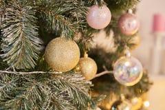 Χρυσό υπόβαθρο Χριστουγέννων των de-στραμμένων φω'των με το διακοσμημένο δέντρο Στοκ Φωτογραφία