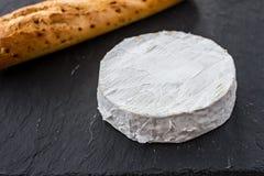 Χρυσό φρέσκο τριζάτο baguette και ελβετικό Camembert τυρί σε ένα μαύρο κατασκευασμένο υπόβαθρο Στοκ εικόνες με δικαίωμα ελεύθερης χρήσης