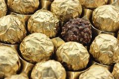 Χρυσό φύλλο αλουμινίου στις γλυκές σοκολάτες στοκ εικόνες