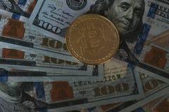 Χρυσό bitcoin σε μας υπόβαθρο λογαριασμών εκατό δολαρίων Νέο virtua Στοκ Φωτογραφίες