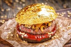 Χρυσό burger βόειου κρέατος με ένα μαύρο κουλούρι, με το arugula και το τυρί και το κέτσαπ που ψεκάζονται με τα καρύδια πεύκων πο Στοκ Εικόνες