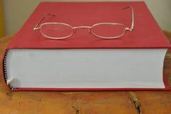Χρυσό eyeglass πλαισίων στο κόκκινο βιβλίο Στοκ εικόνες με δικαίωμα ελεύθερης χρήσης