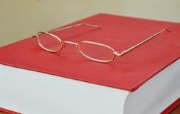 Χρυσό eyeglass πλαισίων στο κόκκινο βιβλίο Στοκ φωτογραφίες με δικαίωμα ελεύθερης χρήσης