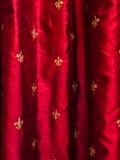 Χρυσό fleur de lis στις κόκκινες κουρτίνες μεταξιού Στοκ Φωτογραφία