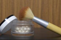 Χρυσό highlighter υπό μορφή σφαιρών σε ένα ανοικτό βάζο Δίπλα σε το είναι μια καλλυντική βούρτσα για την εφαρμογή του Στοκ Φωτογραφία