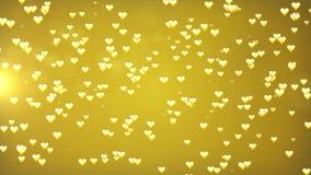 Χρυσό loopable αφηρημένο υπόβαθρο ημέρας βαλεντίνων ` s Οι καρδιές και ακτινοβολούν φω'τα ή bokeh μόρια απεικόνιση αποθεμάτων