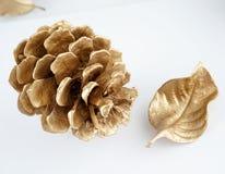 Χρυσό pinecone και χρυσό φύλλο τα Χριστούγεννα διακοσμούν τις φρέσκες βασικές ιδέες διακοσμήσεων η ανασκόπηση απομόνωσε το λευκό Στοκ εικόνα με δικαίωμα ελεύθερης χρήσης