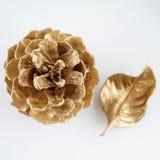 Χρυσό pinecone και χρυσό φύλλο τα Χριστούγεννα διακοσμούν τις φρέσκες βασικές ιδέες διακοσμήσεων η ανασκόπηση απομόνωσε το λευκό Στοκ Εικόνα