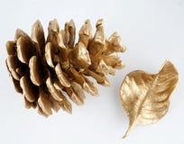 Χρυσό pinecone και χρυσό φύλλο τα Χριστούγεννα διακοσμούν τις φρέσκες βασικές ιδέες διακοσμήσεων η ανασκόπηση απομόνωσε το λευκό Στοκ Φωτογραφία