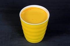 Χρυσό turmeric γάλα σε ένα κίτρινο φλυτζάνι σε έναν γκρίζο στοκ φωτογραφίες