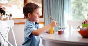 Χρωματίζοντας αυγά αγοριών παιδάκι για τις διακοπές Πάσχας στην εσωτερική κουζίνα Στοκ φωτογραφία με δικαίωμα ελεύθερης χρήσης