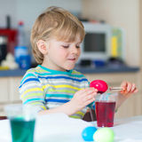 Χρωματίζοντας αυγά αγοριών παιδάκι για τις διακοπές Πάσχας Στοκ φωτογραφία με δικαίωμα ελεύθερης χρήσης