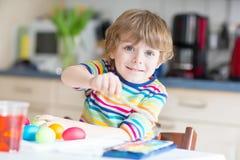 Χρωματίζοντας αυγά αγοριών παιδάκι για τις διακοπές Πάσχας Στοκ Εικόνες