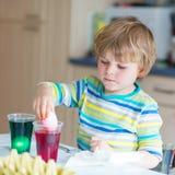 Χρωματίζοντας αυγά αγοριών παιδάκι για τις διακοπές Πάσχας Στοκ Εικόνα
