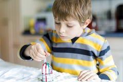 Χρωματίζοντας αυγά λίγων ξανθά αγοριών παιδιών για τις διακοπές Πάσχας στην εσωτερική κουζίνα, στο εσωτερικό Στοκ Φωτογραφία