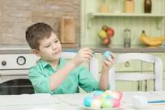 Χρωματίζοντας αυγά λίγων ξανθά αγοριών παιδιών για τις διακοπές Πάσχας στην εσωτερική κουζίνα Στοκ Φωτογραφίες