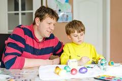 Χρωματίζοντας αυγά λίγων ξανθών προσχολικών παιδιών αγοριών και πατέρων για τις διακοπές Πάσχας Στοκ εικόνα με δικαίωμα ελεύθερης χρήσης