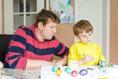 Χρωματίζοντας αυγά λίγων ξανθών προσχολικών παιδιών αγοριών και πατέρων για τις διακοπές Πάσχας Στοκ Φωτογραφίες