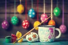Χρωματίζοντας αυγά Πάσχας και κρεμώντας ζωηρόχρωμα αυγά στο υπόβαθρο Στοκ φωτογραφίες με δικαίωμα ελεύθερης χρήσης