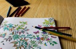 Χρωματίζοντας βιβλίο και μολύβια χαλάρωσης Ο υπολογιστής ταμπλετών είναι πλησίον Στοκ Φωτογραφία