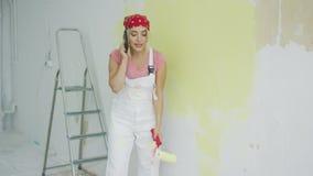 Χρωματίζοντας γυναίκα τοίχων που μιλά στο smartphone απόθεμα βίντεο