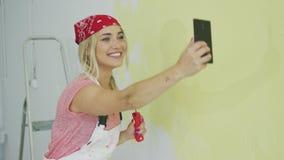 Χρωματίζοντας γυναίκα τοίχων που παίρνει selfie φιλμ μικρού μήκους