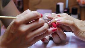 Χρωματίζοντας καρφιά Όμορφη γυναίκα εκμετάλλευσης μανικιούρ η κύρια δαχτυλίδι-finge-χτυπά απόθεμα βίντεο