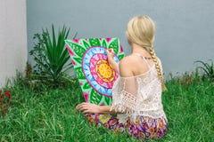 Χρωματίζοντας υπαίθρια, μια νέα γυναίκα ξανθή επισύρει την προσοχή ένα mandala στη συνεδρίαση φύσης στη χλόη ελεύθερη απεικόνιση δικαιώματος