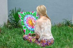 Χρωματίζοντας υπαίθρια, μια νέα γυναίκα ξανθή επισύρει την προσοχή ένα mandala στη συνεδρίαση φύσης στη χλόη διανυσματική απεικόνιση