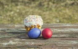 Χρωματισμένα αυγά και κέικ σε έναν ξύλινο πίνακα στοκ εικόνες