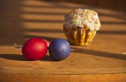 Χρωματισμένα αυγά και κέικ σε έναν ξύλινο πίνακα στοκ φωτογραφίες με δικαίωμα ελεύθερης χρήσης